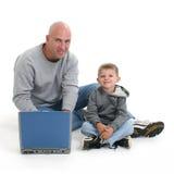 Pai e filho com computador portátil imagem de stock