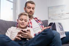 Pai e filho com jornal e smartphone foto de stock royalty free
