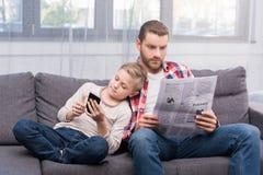 Pai e filho com jornal e smartphone fotografia de stock