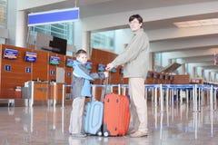 Pai e filho com a mala de viagem no salão do aeroporto Fotos de Stock Royalty Free