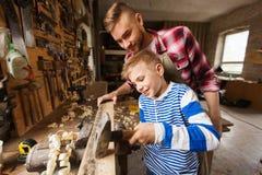 Pai e filho com o martelo que trabalha na oficina Imagem de Stock