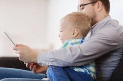 Pai e filho com o PC da tabuleta que joga em casa Imagem de Stock