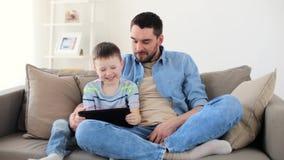 Pai e filho com o PC da tabuleta que joga em casa filme