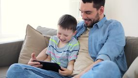 Pai e filho com o PC da tabuleta que joga em casa video estoque