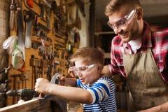 Pai e filho com o plano que barbeia a madeira na oficina imagem de stock royalty free