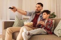 Pai e filho com pipoca que olham a tev? em casa fotografia de stock