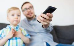 Pai e filho com a tevê de observação remota em casa Imagens de Stock Royalty Free