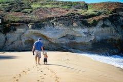 Pai e filho da criança de 2 anos que anda ao longo da areia na praia de b fotos de stock