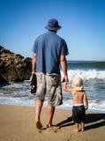 Pai e filho da criança de 2 anos que enfrenta ondas de oceano na praia de b imagem de stock royalty free