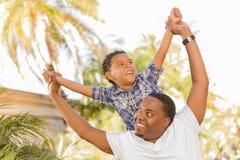 Pai e filho da raça misturada que jogam às cavalitas Fotos de Stock