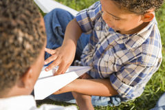 Pai e filho da raça misturada que jogam os aviões de papel Fotografia de Stock