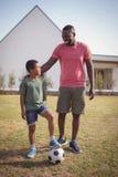 Pai e filho de sorriso que estão no jardim com futebol imagem de stock royalty free