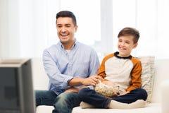 Pai e filho de sorriso que olham a tevê em casa imagens de stock