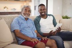 Pai e filho de sorriso que sentam-se no sofá com a tabuleta digital na sala de visitas imagem de stock