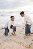 Pai e filho do African-American que jogam na praia fotografia de stock royalty free