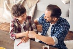 Pai e filho em casa que sentam-se na perfuração da tabela brincalhão ao fazer trabalhos de casa fotografia de stock royalty free