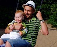 Pai e filho em um balanço Fotografia de Stock Royalty Free