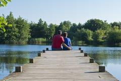 Pai e filho em um cais de madeira em uma lagoa Fotografia de Stock Royalty Free