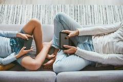 Pai e filho Losted nos dispositivos eletrónicos Sitti de duas pessoas imagem de stock royalty free