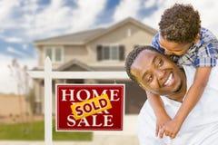 Pai e filho na frente do sinal dos bens imobiliários, casa fotografia de stock royalty free