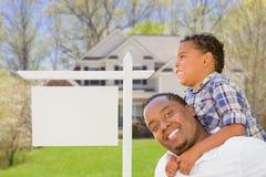 Pai e filho na frente do sinal e da casa vazios de Real Estate fotografia de stock royalty free