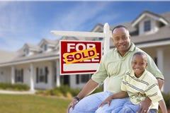 Pai e filho na frente do vendido para o sinal e a casa da venda Fotos de Stock Royalty Free