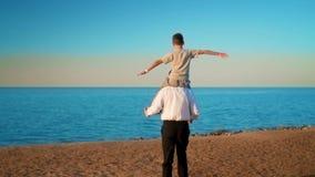 Pai e filho na praia no por do sol video estoque