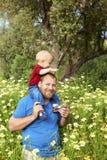 Pai e filho nas flores Imagens de Stock Royalty Free