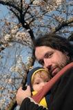Pai e filho no estilingue do bebê sob sakura Fotos de Stock Royalty Free