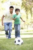 Pai e filho no parque com esfera de futebol imagens de stock