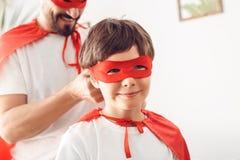 Pai e filho nos trajes do superheroe em casa que estão o homem feliz de sorriso do quando do close-up do menino que amarra o nó e fotos de stock royalty free