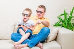 Pai e filho nos vidros 3D que olham a tevê Foto de Stock