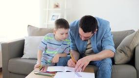 Pai e filho pequeno com desenho de pastéis em casa video estoque