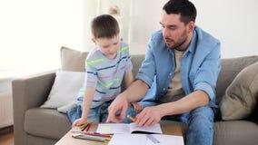 Pai e filho pequeno com desenho de pastéis em casa filme