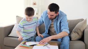 Pai e filho pequeno com desenho de pastéis em casa vídeos de arquivo
