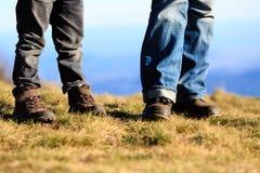 Pai e filho pequeno que caminham botas nas montanhas Foto de Stock Royalty Free