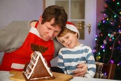 Pai e filho pequeno que preparam uma casa da cookie do pão-de-espécie Foto de Stock
