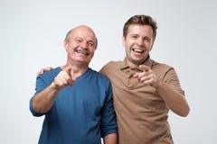 Pai e filho que apontam na câmera com finge do índice imagem de stock royalty free
