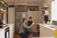 Pai e filho que arranjam pratos sujos na máquina de lavar louça foto de stock