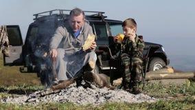 Pai e filho que comem o pão roasted ao lado da fogueira video estoque