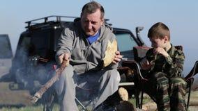 Pai e filho que comem o pão roasted ao lado da fogueira filme