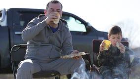 Pai e filho que comem a soda roasted do pão e da bebida ao lado da fogueira filme