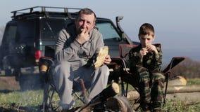 Pai e filho que comem a soda roasted do pão e da bebida ao lado da fogueira video estoque