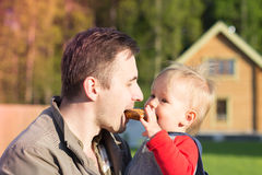 Pai e filho que comem um bagel para dois Fotos de Stock
