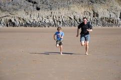 Pai e filho que competem na praia Fotografia de Stock
