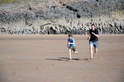 Pai e filho que competem na praia Fotografia de Stock Royalty Free