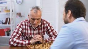 Pai e filho que competem na xadrez, no passatempo do fim de semana e na atividade de lazer, tradição vídeos de arquivo