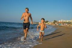 Pai e filho 4-5 que correm na praia, tendo o tempo da família da qualidade junto EUA Por do sol Dia ensolarado do verão bonito, m fotografia de stock royalty free