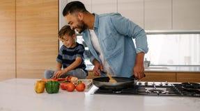 Pai e filho que cozinham junto na cozinha foto de stock