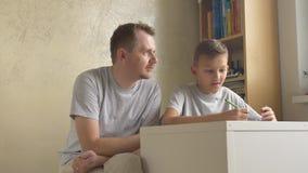 Pai e filho - pai que dá o conselho ao menino na mesa na sala vídeos de arquivo